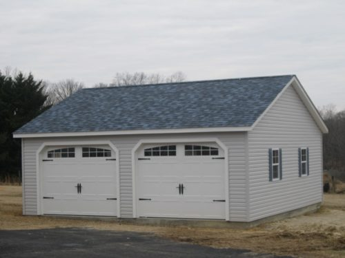 two garage garage with doors and asphalt shingles