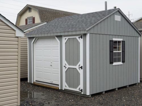 grey amish built cottage garage sitting on gravel