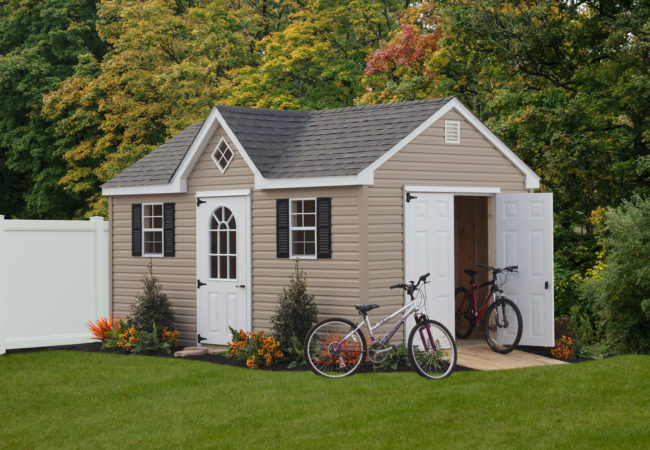a frame dormer shed with white doors and bikes