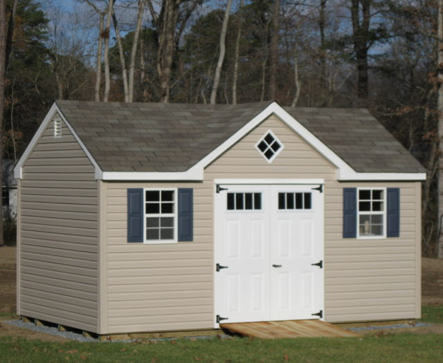 tan a frame dormer shed with white doors in front of trees