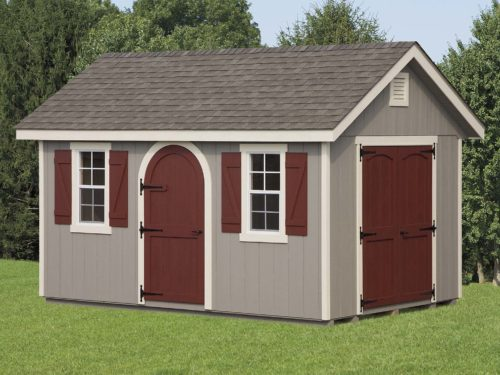 grey classic cottage shed with maroon doors in front of trees