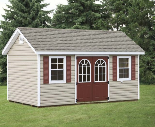 tan classic cottage shed with maroon doors and asphalt shingles