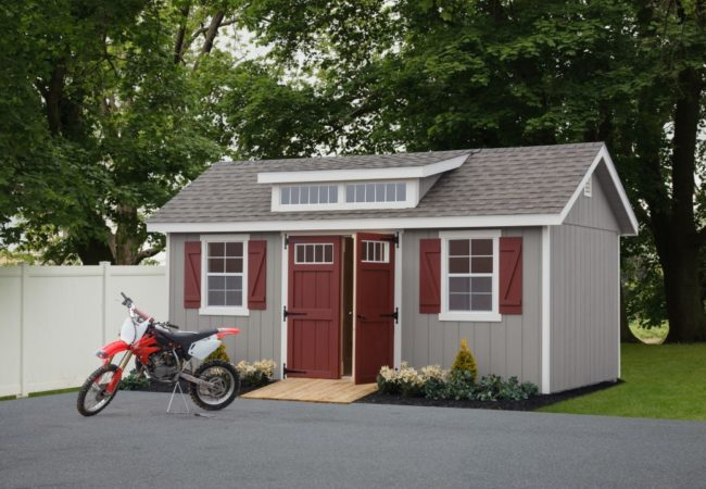 classic studio dormer shed with maroon doors and dirtbike