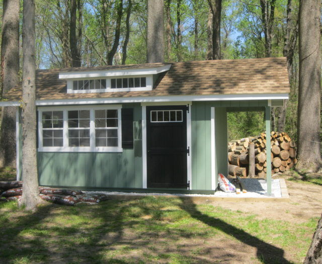 green classic studio dormer shed with pile of wood in back