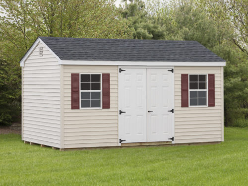 tan cottage shed with double white front doors