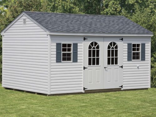 grey cottage shed sitting on lawn in backyard