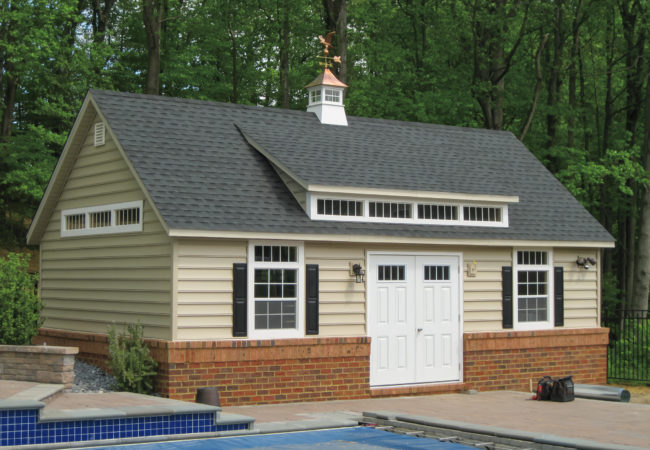 custom classic cottage shed sitting next to swimming pool