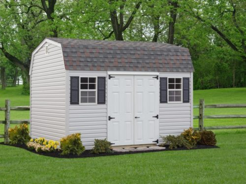 backyard dutch barn shed with white double doors sitting in front of fence