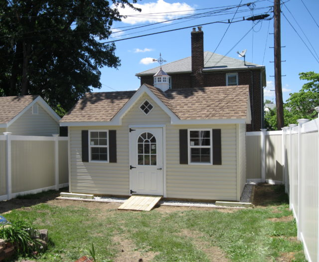 classic a frame dormer shed with white door in backyard