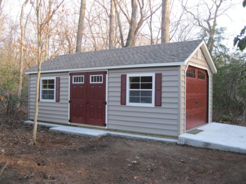 amish built classic cottage garage with red doors and concrete ramp