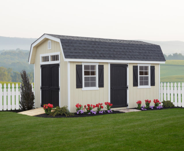 classic dutch barn shed in front of white picket fence