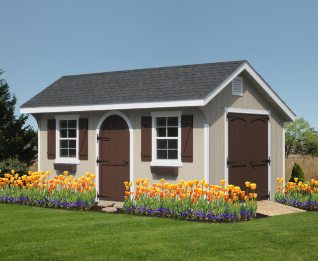 classic quaker shed with brown doors and flowers in front