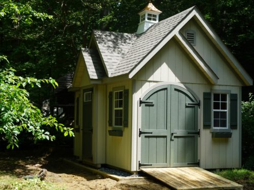 alpine shed with green doors sitting in shade