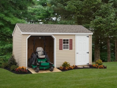 tan 7 cottage garage with green lawnmower
