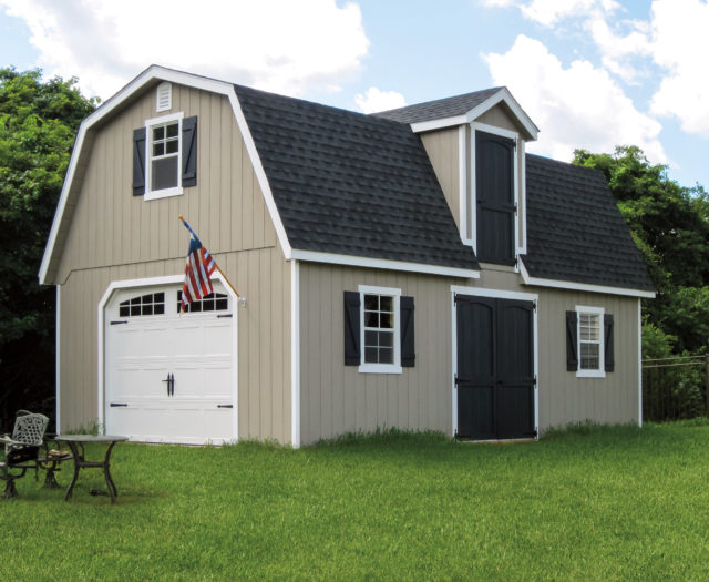 two story dutch barn shed with white garage door and american flag
