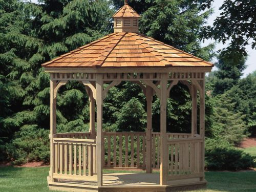 wood gazebo sitting in front of pine trees