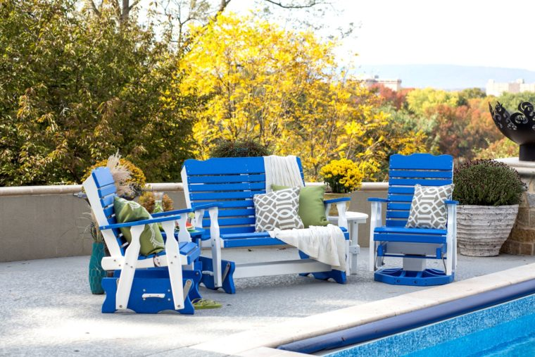 blue and white lawn furniture sitting by pool