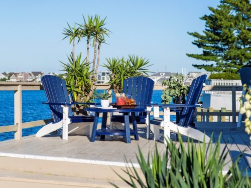 blue outdoor furniture sitting in front of bay on elevated synthetic deck