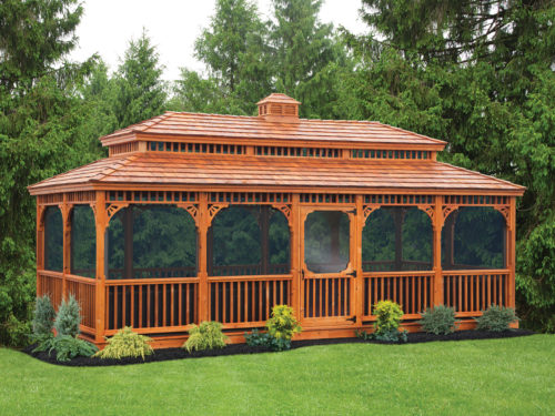 large wooden gazebo with screens sitting in front of trees