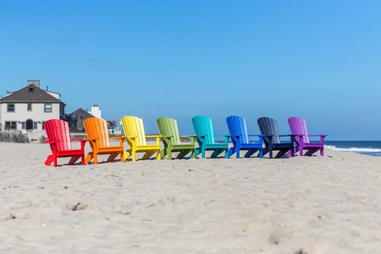 multicolored outdoor furniture sitting on beach in front of shore homes