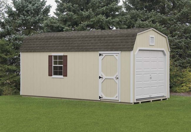tan dutch barn garage with white door and asphalt shingles sitting green grass