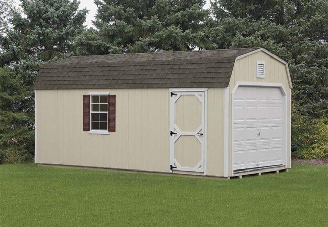 tan dutch barn garage with white door and asphalt shingles sitting green grass