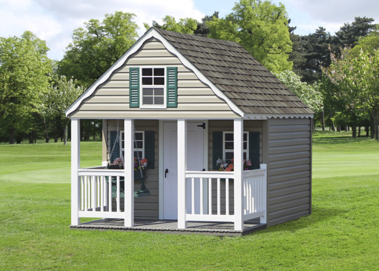 a frame playhouse with white door and porch posts