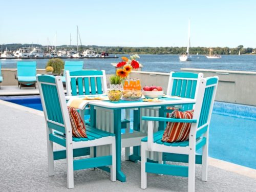 teal and white lawn furniture sitting next to pool overlooking the bay