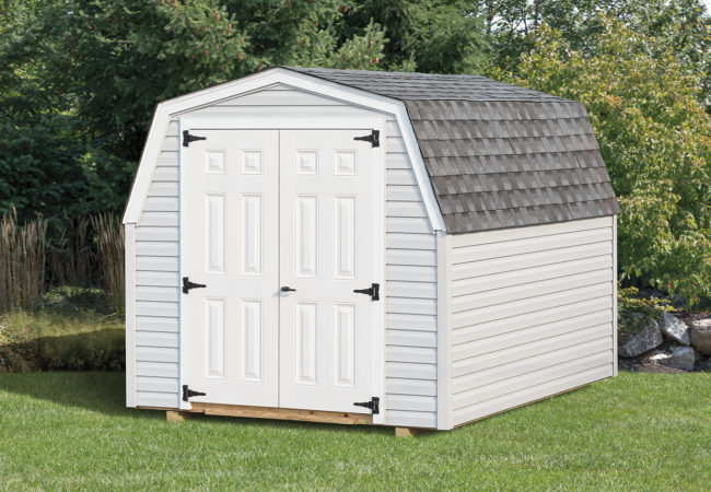 white mini barn shed sitting in backyard
