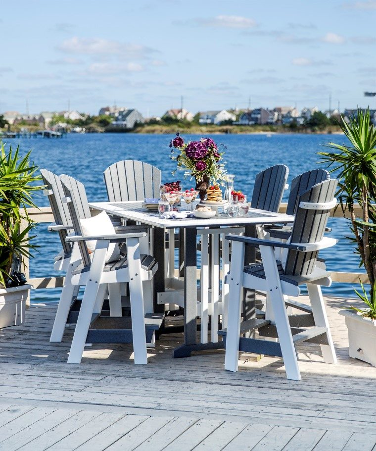 white outdoor furniture set sitting on deck overlooking the bay