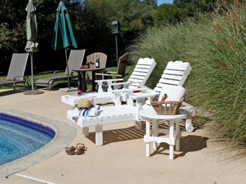 white outdoor lawn furniture sitting between pool and outdoor foliage