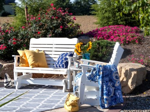 lawn furniture in backyard with pillows and blanket