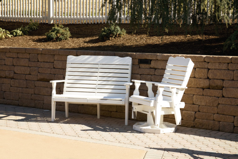 white outdoor furniture in front of retaining wall