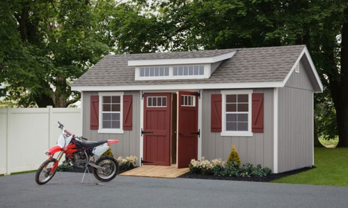 backyard man cave shed with red dirt bike parked out front