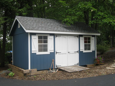 blue shed with white doors beneath trees