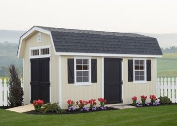man cave shed with black doors and flowers out front